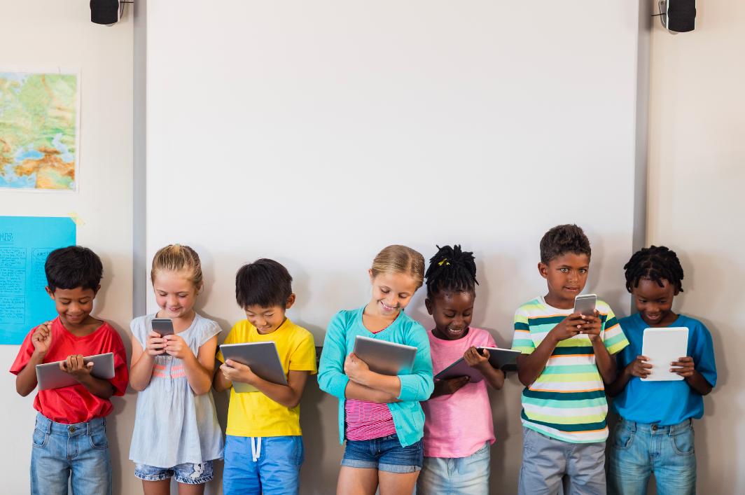 Ragazzi e ragazze con smartphone e tablet in classe